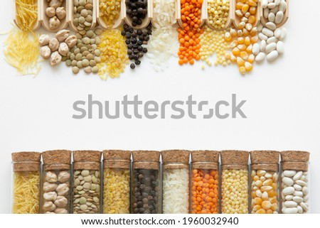 Dried beans, couscous pasta, unexploded corn, red lentil, rice, black pepper, bulgur, green lentils, chickpeas, vermicelli, on white background in glass bell jar and wooden legume spoons Stock photo ©