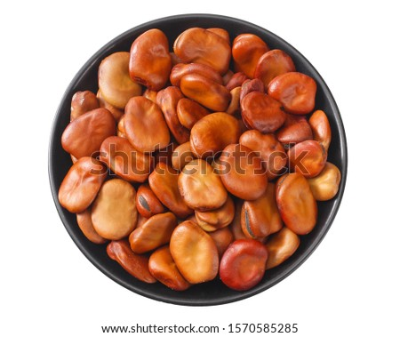 dried broad beans in black bowl isolated on white background. top view
