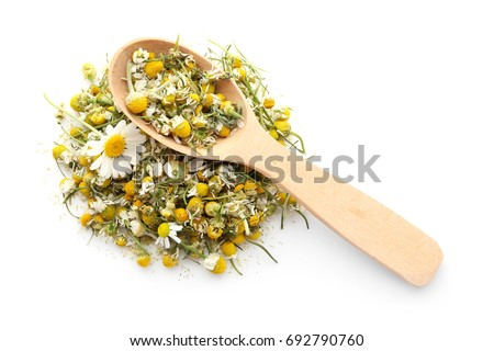 Dried chamomile flowers and wooden spoon on white background