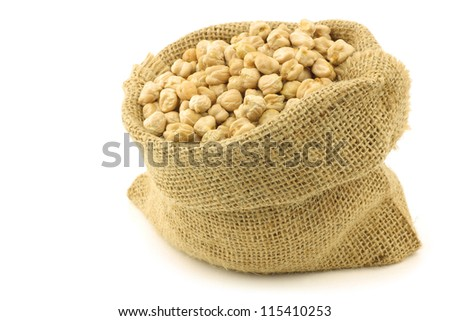 dried chick peas in a burlap bag on a white background