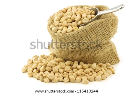 dried chick peas in a burlap bag with an aluminum scoop on a white background - stock photo