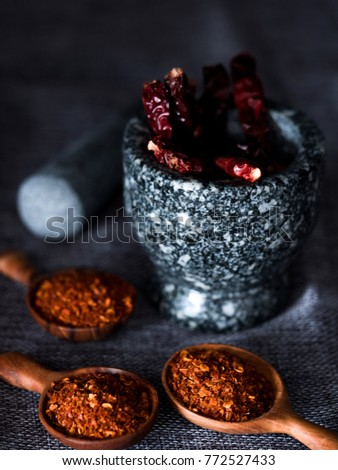 Shutterstock Dried chili pepper power in wooden spoons and dried chili pepper in mortar with a pestle on gray cloth, dark tone with selective focused