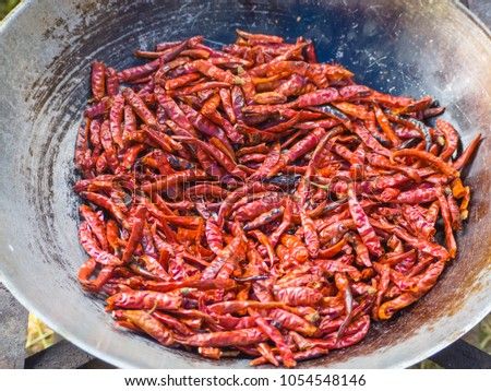 Dried chilies fry on a pan #1054548146