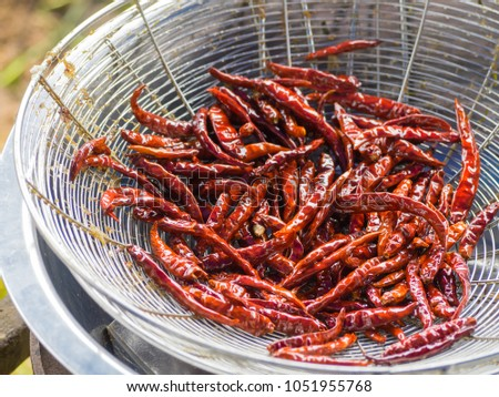 Dried chilies fry on colander #1051955768