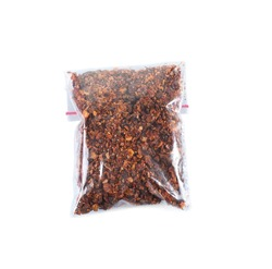 Dried chopped tomatoes in plastic zipper bag, isolated on white
