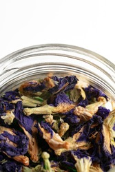 Dried clitoria ternatea, commonly known as Asian pigeonwings, bluebellvine, blue pea, butterfly pea, cordofan pea and Darwin pea close up in a glass jar on a white background. Shallow depth of field