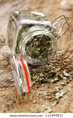 Dried cooking herbs in an opened glass bottle lying on its side spilling out onto an old rustic wooden tabletop