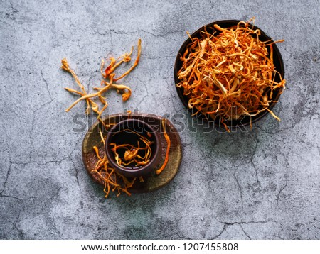 Dried cordyceps militaris on ceramic bowl wih a cup of water, add water from the Ophiocordyceps sinensis extract on top view. Medicinal properties in the treatment of diseases. Healthy concept.