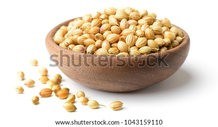 dried coriander seeds in the wooden plate, isolated on white #1043159110