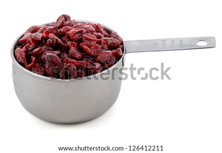 Dried cranberries presented in an American metal cup measure, isolated on a white background