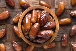 dried date fruit in bowl on wooden table background.