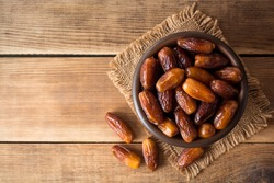 Dried dates fruit in ceramic bowl on wooden table. Top view.