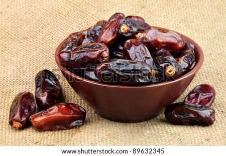 Dried dates in a plate on the linen texture