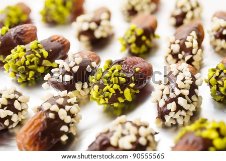 Dried dates with chocolate cover and almond and pistachio slivers on ...