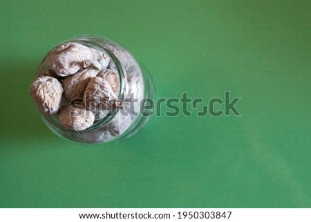 Dried figs coated in powder sugar on glass. Green wooden background Stock foto ©