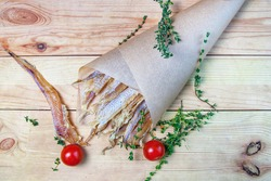 dried fish in a paper bag with tomatoes and rosemary