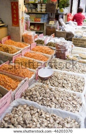 dried fish, nuts, fruit, seeds, and mushrooms displayed in bins on the sidewalk outside a store in Chinatown, New York