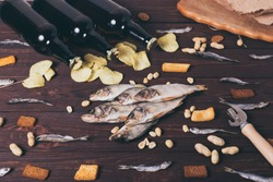 Dried fish, perch, bleak, chips, crackers, nuts and three brown glass bottles of beer on a wooden background. Studio photo.