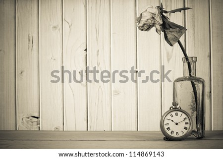 Dried flower in vintage bottle, pocket watch in front of wooden background