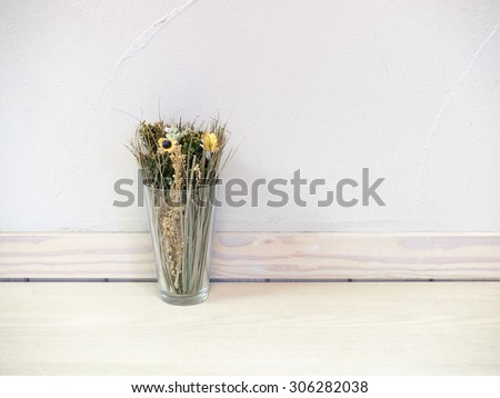 dried flowers and grasses in transparent glass over wooden table with concrete wall background