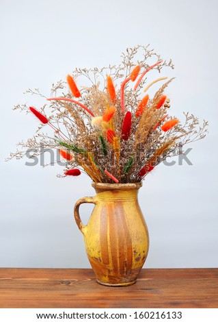 Dried flowers in a ceramic vase on the table
