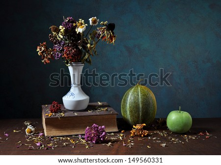 Dried flowers in a vase and books on the table