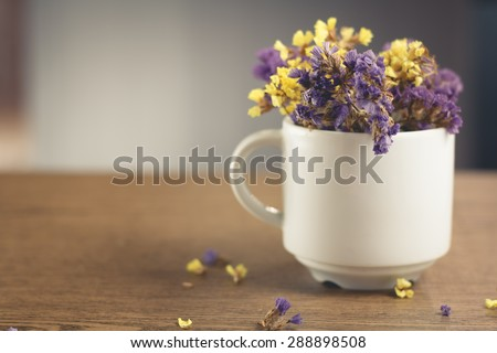 Dried flowers in a white coffee cup and placed on a wooden table.Warm tone photo.