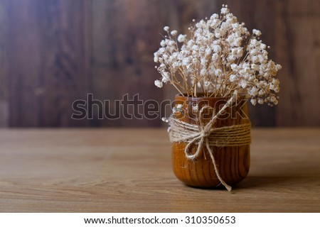 Dried flowers in a wooden vase with a rope on a wooden table. Vintage background.