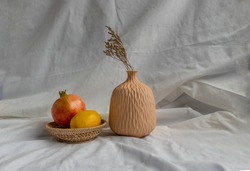 Dried flowers in Handmade Ceramic Vases and Fresh fruits on Wicker basket with white background. Home decor.