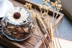 Dried flowers jar on wooden tray with warm morning light near the window.Copy space.