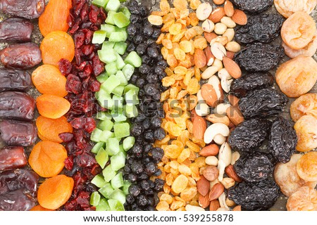 Dried fruit background. Rows of dried dates, apricots,cranberries, pomelos, blueberries, nuts, prunes and figs. #539255878