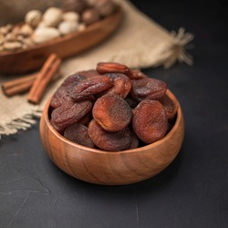 dried fruit in a square wooden bowl on a dark background and burlap