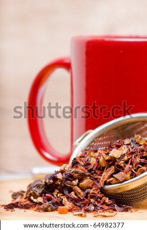 Dried fruit tea in tea strainer with cup of tea
