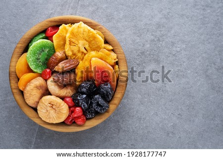 Dried fruits and berries on a wooden bowl top view. Raisins, kiwi, cherries, plums, dried apricots, dates, pineapples, figs, melon.