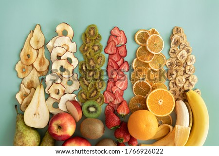 Dried fruits and fruit chips along with the fresh fruit of which they are made. Dietary nutrition. Natural and healthy snack food.