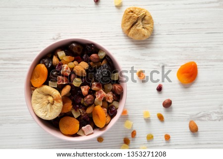 Dried fruits and nut mix in a pink bowl on white wooden background, top view. Overhead, from above, overhead.  #1353271208