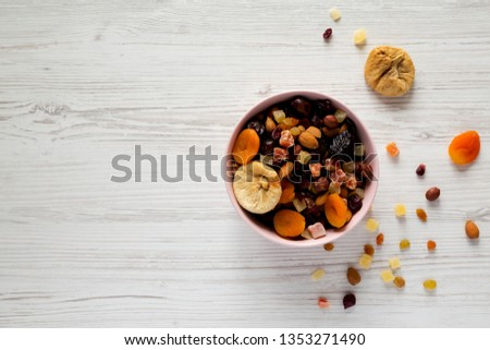 Dried fruits and nut mix in a pink bowl on white wooden background, top view. Overhead, from above, overhead. Copy space. #1353271490