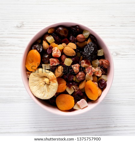 Dried fruits and nuts in a pink bowl over white wooden surface. Top view, from above, flat lay. Close-up.