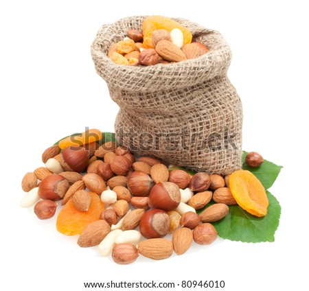 dried fruits and nuts in linen basket on green leaves isolated on white background