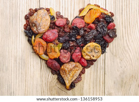 Dried fruits in the shape of hearts on a wooden background
