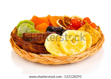 Dried fruits on wicker plate isolated on white - stock photo