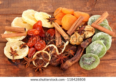 Dried fruits with cinnamon and anise stars on wooden background - stock photo