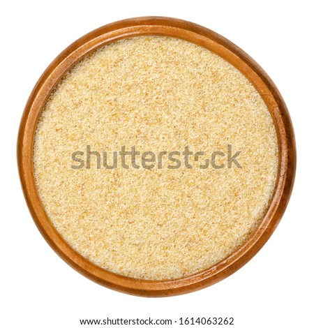Dried garlic granules in wooden bowl. Allium sativum, with its pungent flavor is used as seasoning or condiment and also in medicine. Isolated macro food photo, closeup from above on white background.