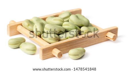 dried green faba beans in the wooden plate, isolated on white background