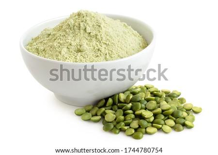Dried green pea flour in a white ceramic bowl next to a pile of green split peas isolated on white. Stockfoto ©