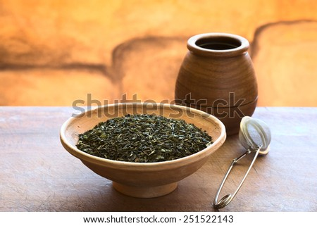 Dried green tea leaves in bowl with a tea strainer and wooden tea cup photographed with natural light (Selective Focus, Focus one third into the tea leaves)