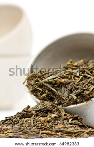 Dried green tea leaves in ceramic cup over white background