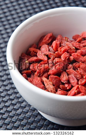 Dried healthy Goji fruits in a white bowl.
