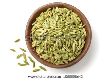 dried herb, fennel seeds in the wooden plate, isolated on white, top view