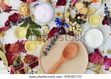 Dried herb mix, wooden plate spoon, moisturizer, lotion, essential oils. Herbal skincare spa preparation, top view.